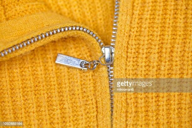 close-up of zipper on yellow sweater - ファスナー ストックフォトと画像