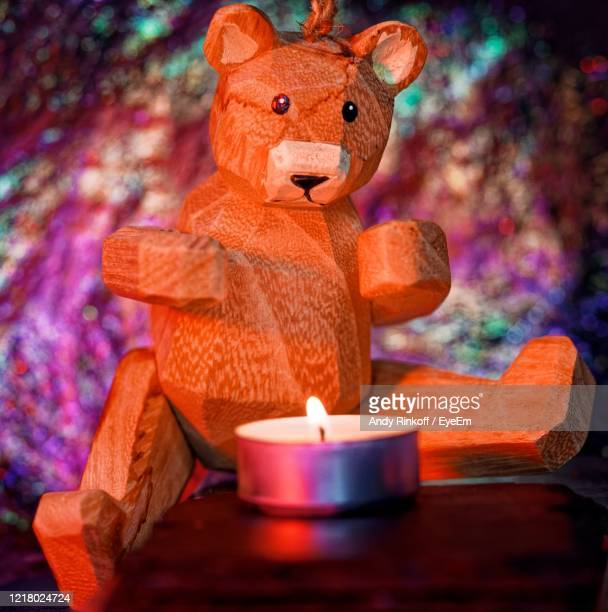 close-up oftoy wooden bear warming paws by a  burning candle . colourful background. - andy rinkoff stock pictures, royalty-free photos & images