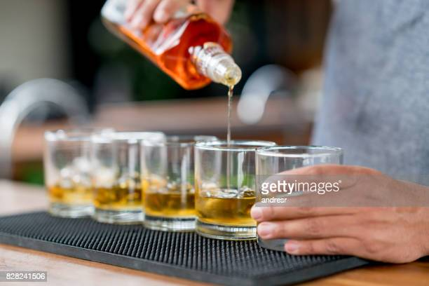 close-up on a bartender serving drinks at a bar - rum stock pictures, royalty-free photos & images