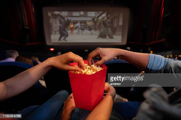 close-up on a couple at the movies eating popcorn - film industry stock pictures, royalty-free photos & images