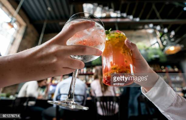 close-up on a couple making a toast at a restaurant - cocktail party stock pictures, royalty-free photos & images