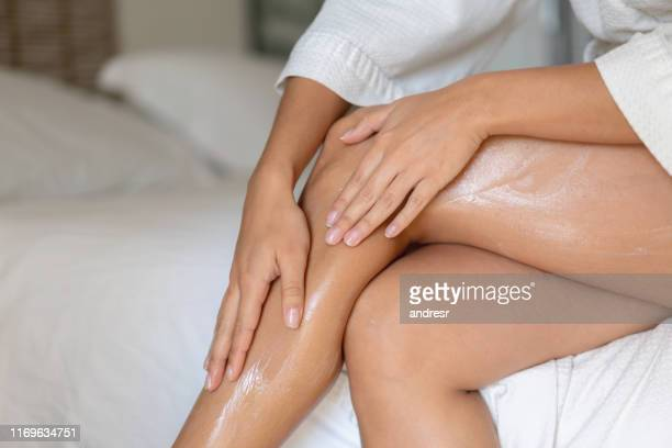 close-up on a woman applying cream on her legs - the human body stock pictures, royalty-free photos & images