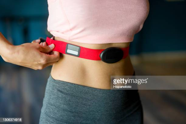 close-up on a woman at the gym putting on a fitness tracker - strap stock pictures, royalty-free photos & images