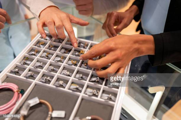 close-up on a woman buying jewels at the jewelry store - jewelry store stock pictures, royalty-free photos & images