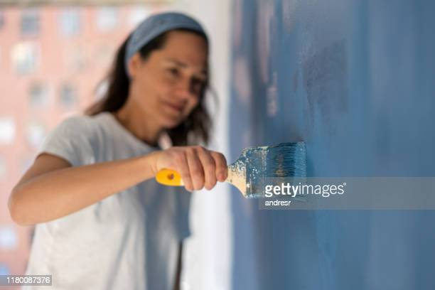 close-up on a woman painting her house - ornato foto e immagini stock