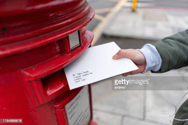 close-up on a woman sending a letter by mail - sending stock pictures, royalty-free photos & images