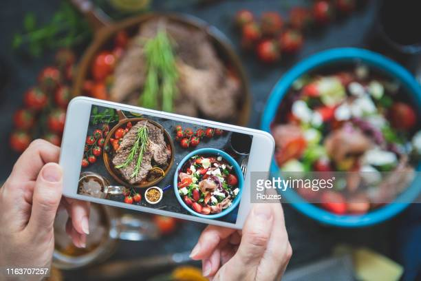 close-up on a woman taking a photo of the food at a restaurant - photography themes stock pictures, royalty-free photos & images