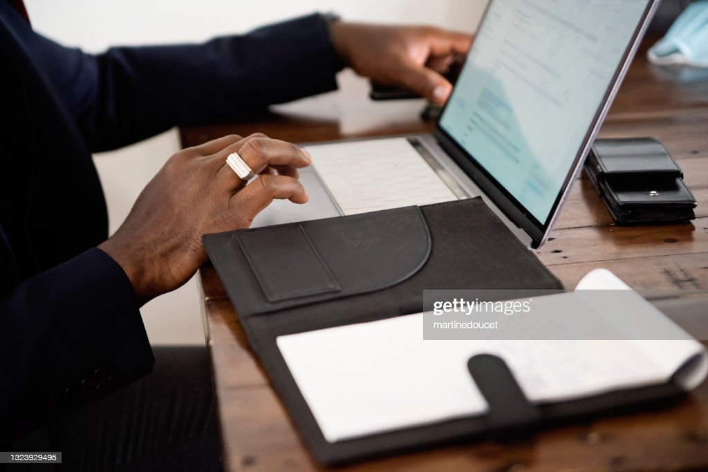Close-up on African-American man's hand working from home. : Stock Photo