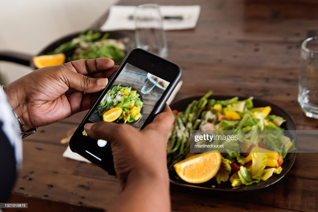 Close-up on African-American woman photographing dish. : Stock Photo