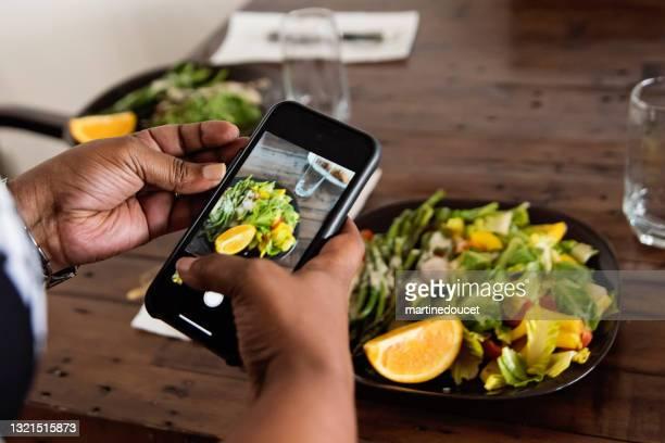 "primer plano de la mujer afroamericana fotografiando el plato. - ""martine doucet"" or martinedoucet fotografías e imágenes de stock"