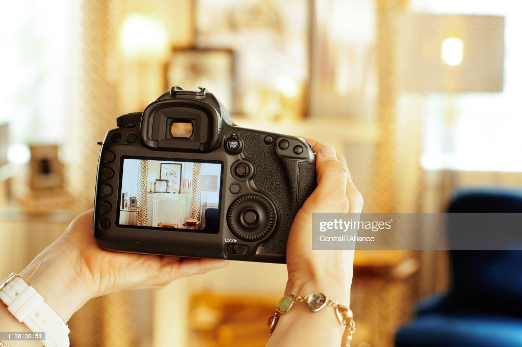 Closeup on DSLR camera in hand of female interior photographer : Stock Photo