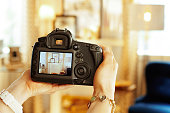 Closeup on DSLR camera in hand of female interior photographer
