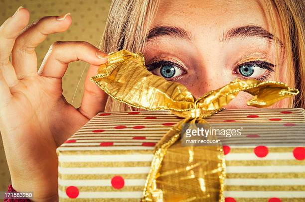 Close-up on eyes and hand opening a wrapped gift.