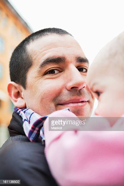 close-up on father with daughter (0-11 months) in his arms - 0 11 monate stock-fotos und bilder