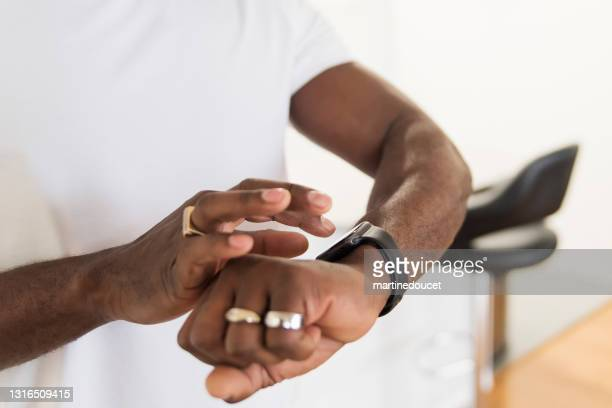 "close-up on man looking at his training watch on white background. - ""martine doucet"" or martinedoucet stock pictures, royalty-free photos & images"