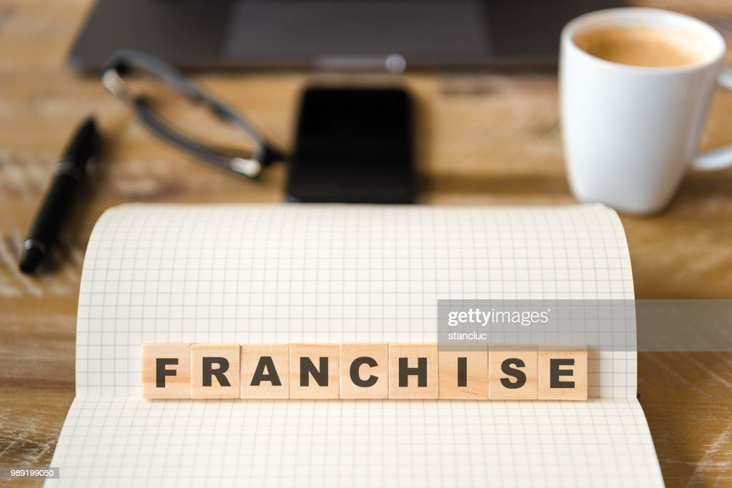 Closeup on notebook over wood table background, focus on wooden blocks with letters making Franchise text : Stock Photo