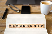 Closeup on notebook over wood table background, focus on wooden blocks with letters making Membership text