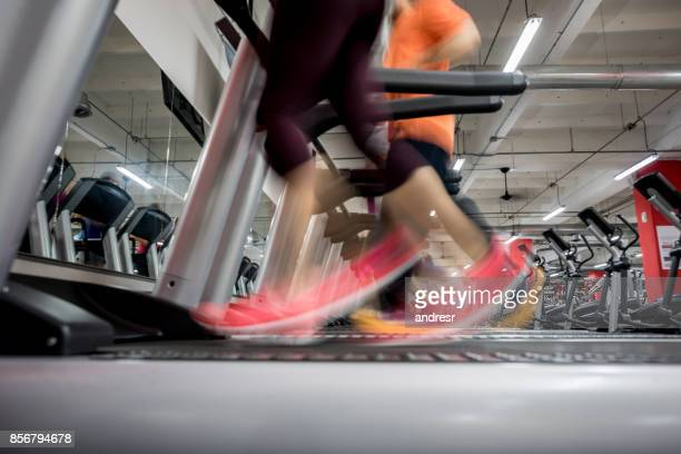 Close-up on people's feet at the gym running on the treadmills