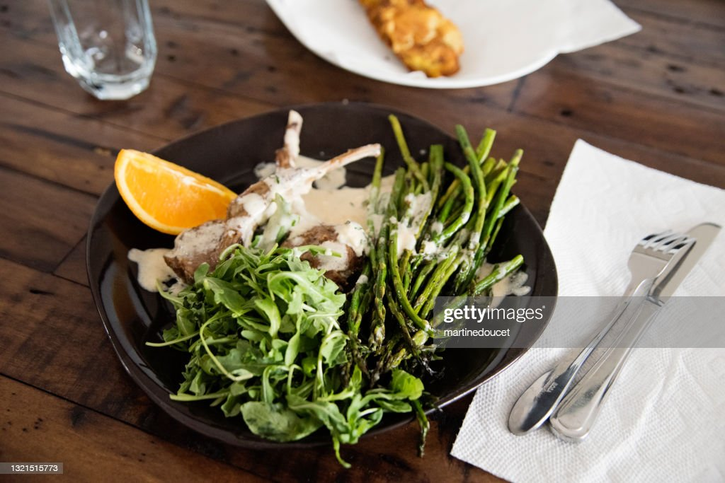 Close-up on plate of lamb chops and salad on a wooden table. : Stock Photo