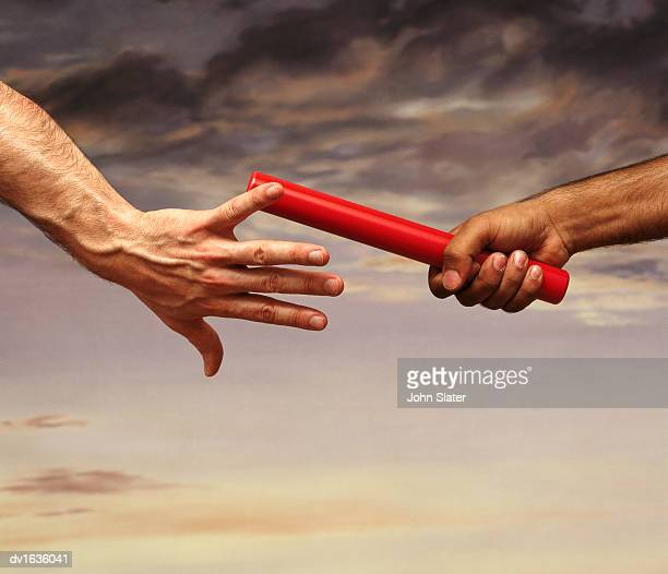 close-up on the hand of a male athlete passing a relay baton to another athlete, with a dramatic sky in the background - passing sport stockfoto's en -beelden
