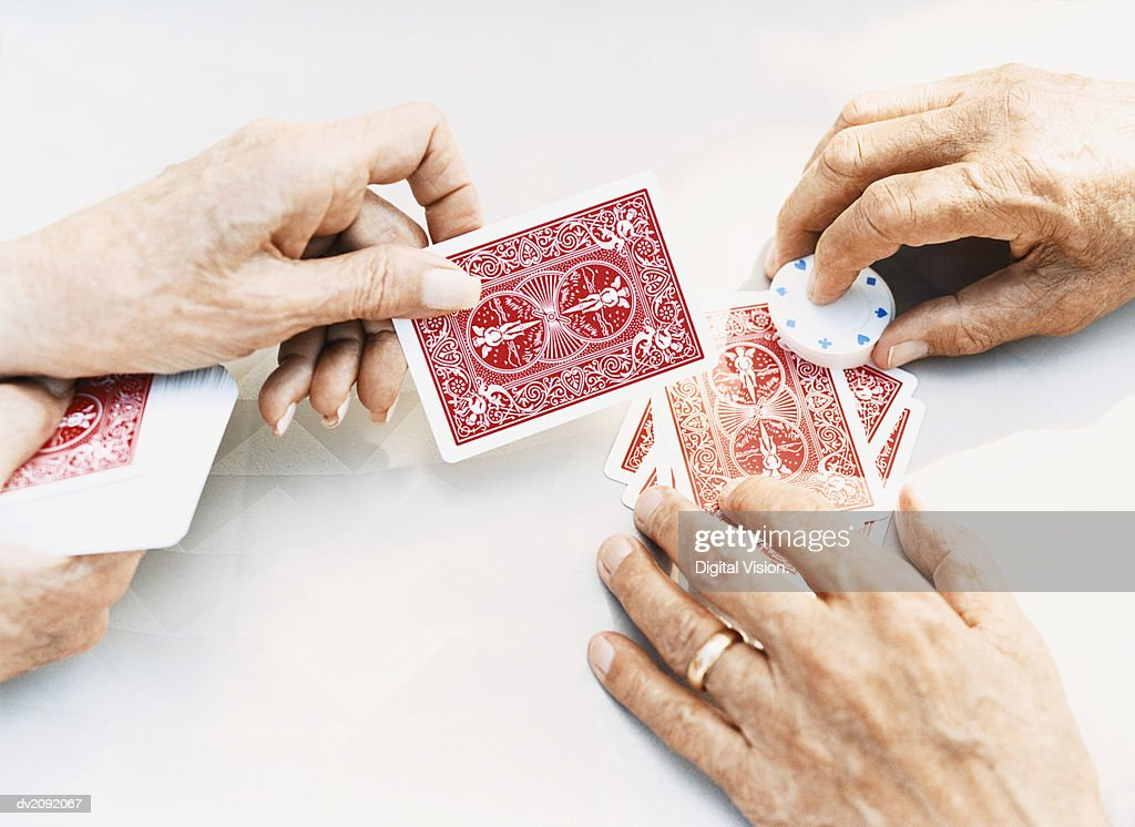 Close-Up on the Hands of a Senior Man and Woman Holding Playing Cards and Gambling Chips : Stock Photo