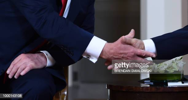 Closeup on US President Donald Trump and Russian President Vladimir Putin shaking hands ahead of their meeting in Helsinki on July 16 2018 The US and...