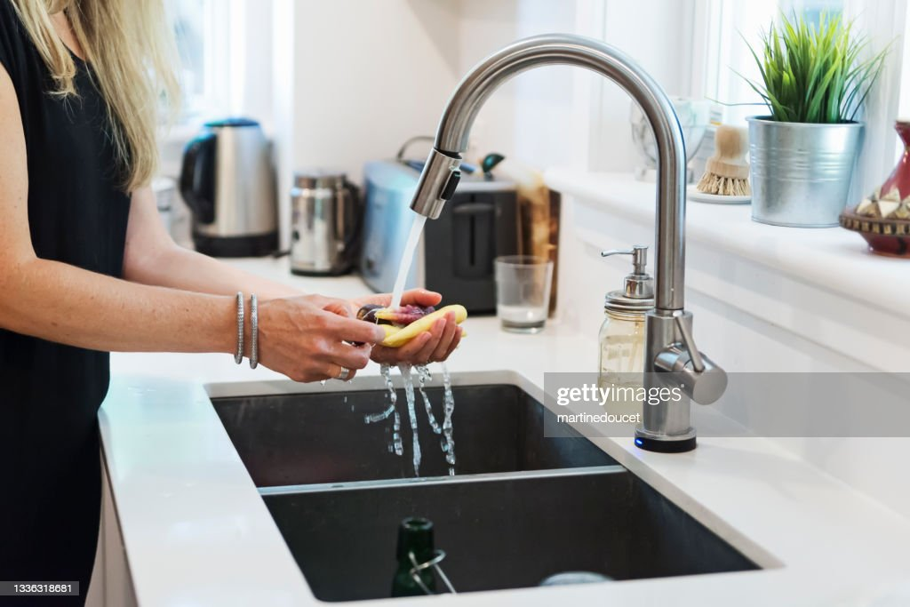 Close-up on woman's hands washing vegetables in home kitchen. : Stock Photo