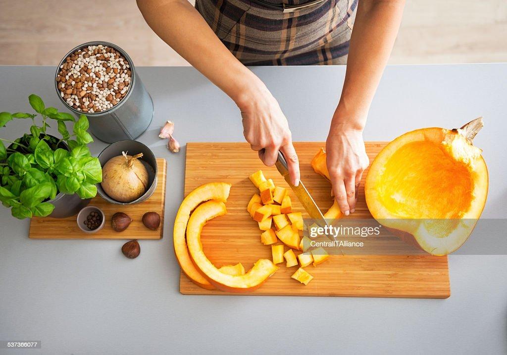 closeup on young housewife cutting pumpkin : Stock Photo