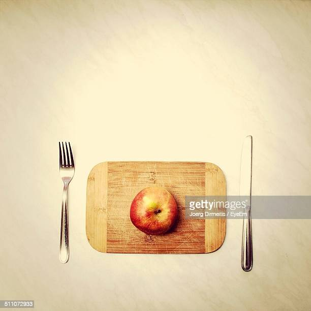 Close-up overhead view of apple with fork and table knife