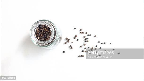 close-up overhead view of black pepper in bottle - pepper seasoning stock photos and pictures