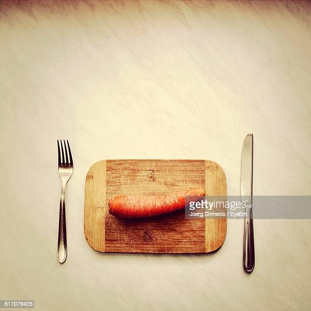 Close-up overhead view of carrot with fork and table knife