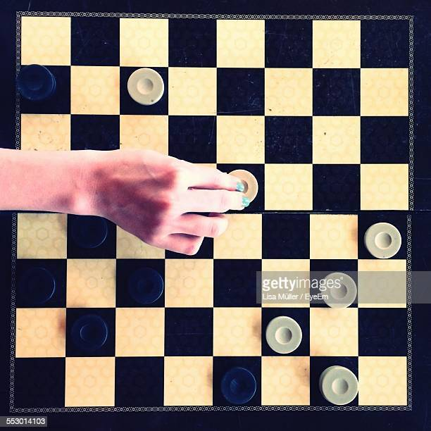 Close-Up Overhead View Of Hand Playing Chess