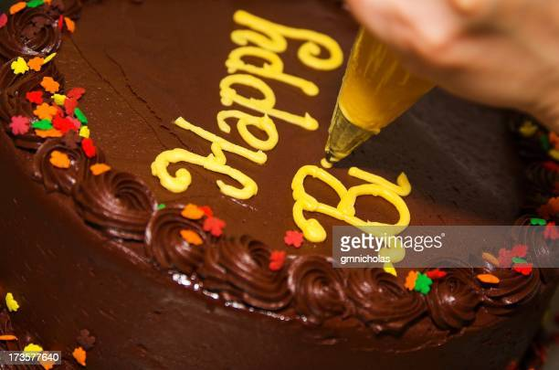 Close-up photo of a decorator writing letters on a cake