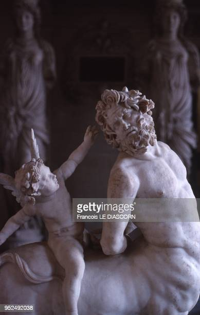 A closeup photo of a roman copy of a Greek statue depicting a centaur with a small cupid on his back Louvre Museum Paris behind the centaur are two...