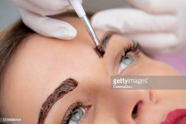 close-up photo of beautician applying dye on woman's eyebrows - stock photo - mid adult women stock pictures, royalty-free photos & images