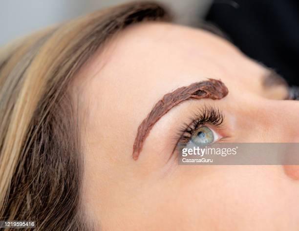 nahaufnahme foto von hair dye auf frau augenbraue - stockfoto - färbemittel stock-fotos und bilder