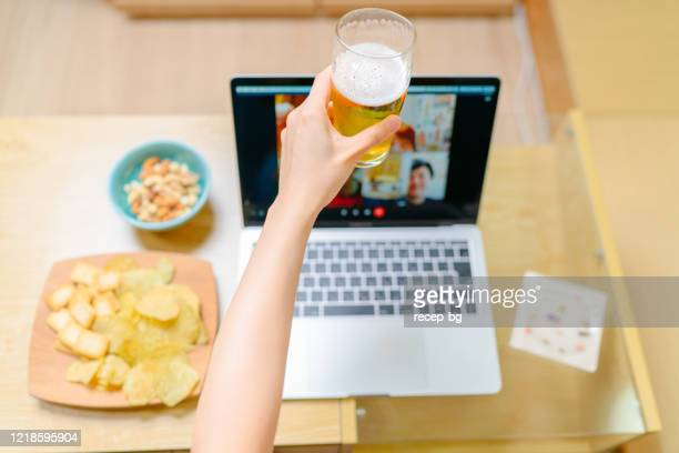 close-up photo of human hand while having fun with loved ones via conference call on laptop at home - corona beer stock pictures, royalty-free photos & images