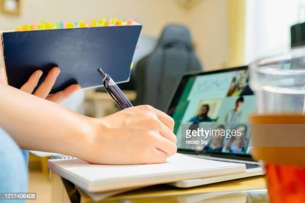 自宅からの電話会議で他の大学生と一緒に勉強しながら、人間の手のクローズアップ写真 - ウェブ会議 ストックフォトと画像