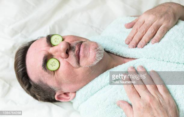 close-up photo of man with homemade cucumber mask on his face. elderly man takes care of his face at home during the quarantine. - lichaamsverzorging stockfoto's en -beelden