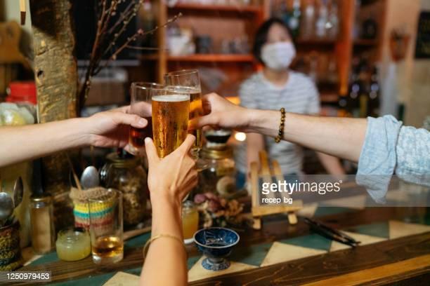 nahaufnahme foto von menschen, die mit bier in der bar mit krankheitspräventionsmaßnahmen jubeln, wird getroffen - corona beer stock-fotos und bilder