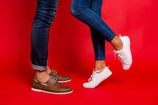 Closeup photo of woman and man legs in jeans, pants and shoes, girl with raised leg, stylish couple kissing during date, isolated over red background, he vs she 925802062
