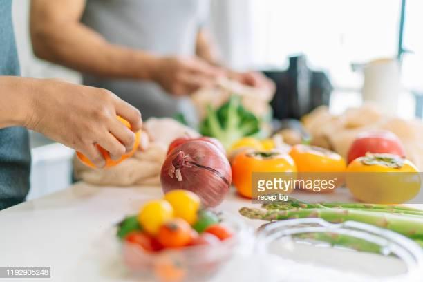 自宅でビーガンフードを準備しながら、女性の手のクローズアップ写真 - 料理 ストックフォトと画像