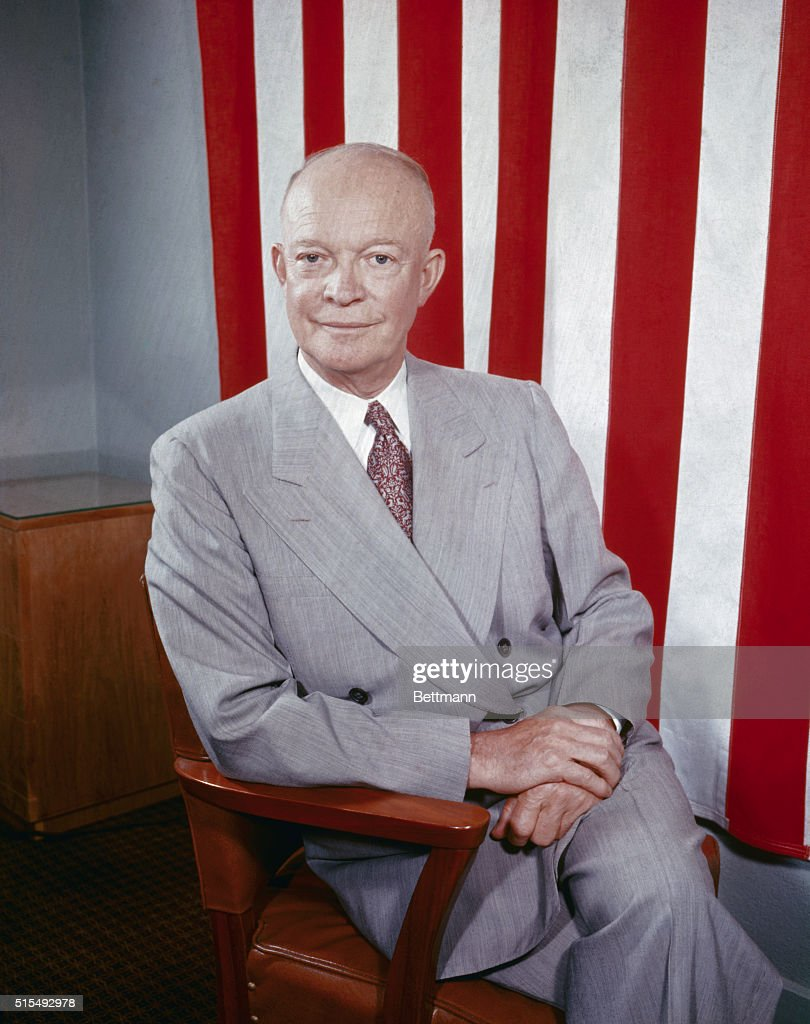 Closeup photograph of former President Eisenhower sitting in front of the American flag.