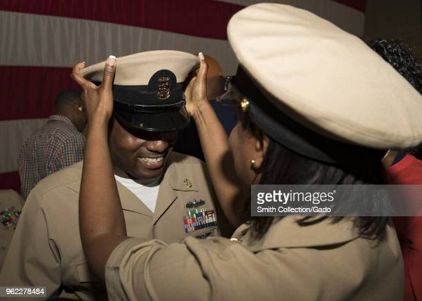 Closeup photograph of Harold McMillan receiving a combination cover from Master Chief Helen Henderson during a pinning ceremony held onboard the USS...