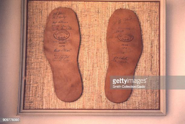 Closeup photograph of two leather shoe insoles a commemorative award signed by members of the EIS' first graduating class in 1951 1953 Image courtesy...