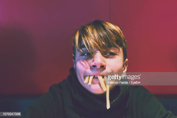 close-up playful boy with french fries in mouth - fries stock-fotos und bilder