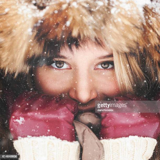 Closeup portrait of a beautiful girl while snowing