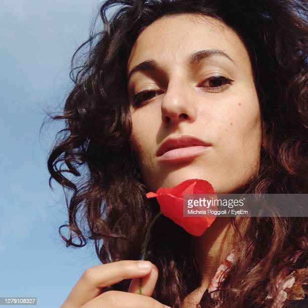 close-up portrait of a beautiful woman with poppy in her hand - eye liner stock pictures, royalty-free photos & images