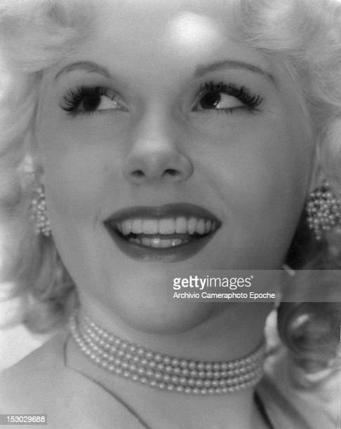 Closeup portrait of a blonde woman wearing pearls earrings and choker cira 1948