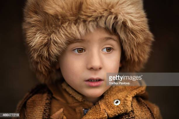 closeup portrait of a child with a large fur hat - fur hat stock photos and pictures